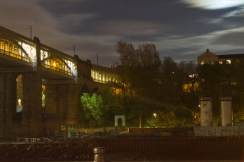 The High Level Bridge stretches across the river under the moonlight