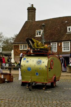A performer folds herself into a suitcase, on top of a tiny caravan, outside Battle Abbey