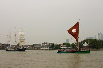 Thalassa dwarfs the smaller vessel leading it